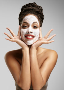 fun black woman with a facial mask