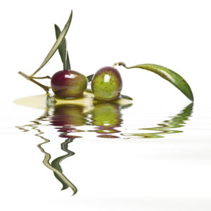 Green olives with leaves covered in olive oil and reflected on water.
